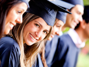 Woman standing out from a graduation group smiling