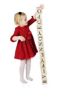 An adorable and dressed up preschooler creating a tower out of a